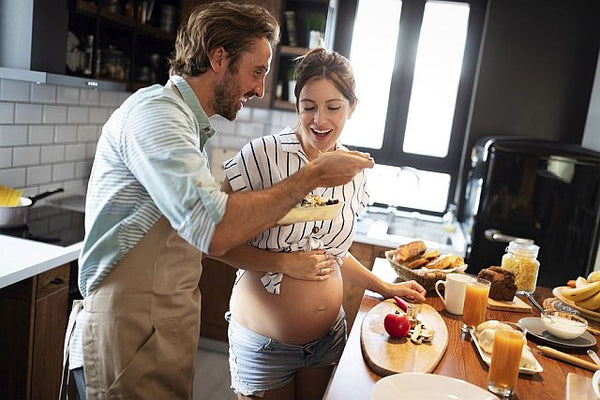pregnant woman and partner tasting food in the kitchen