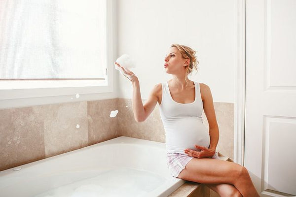 pregnant woman blowing soap bubbles whilst sat on the side of a white bath