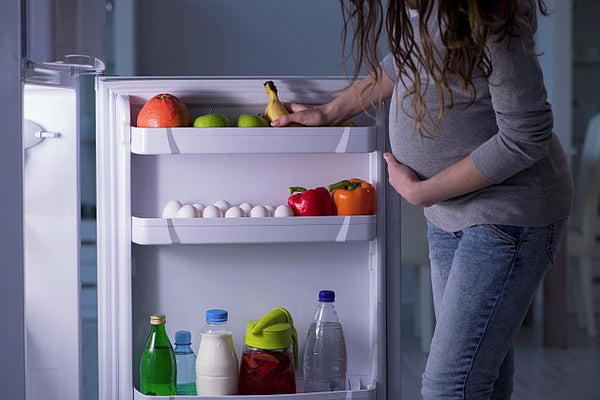 4. pregnant lady standing at an open fridge looking at food inside