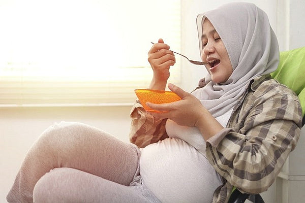 pregnant woman eating from an orange bowl
