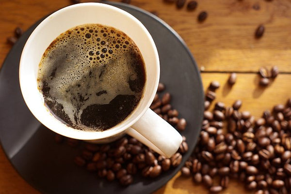 Black coffee surrounded by coffee beans