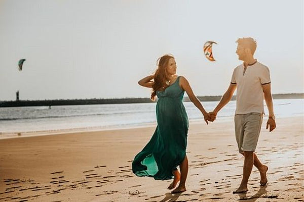 Pregnant couple walking hand in hand on beach