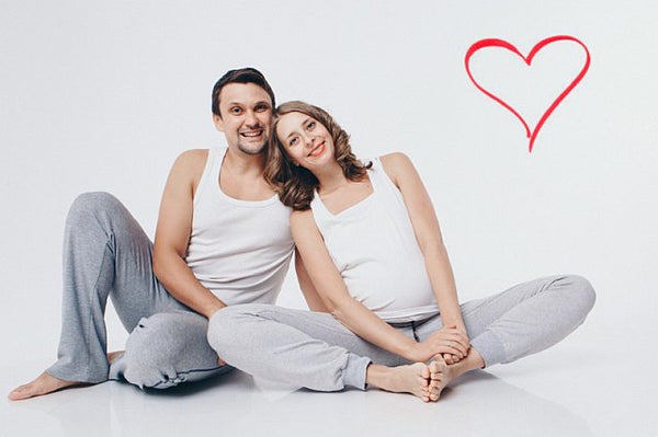 Pregnant couple sat on floor in yoga gear