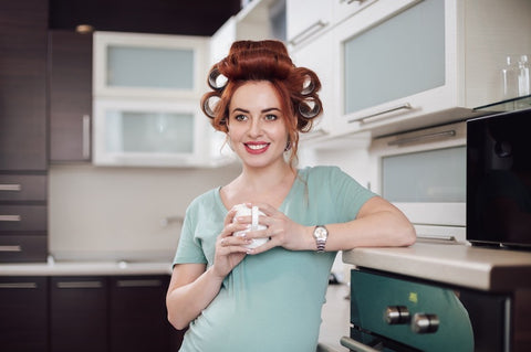 woman with rollers,holding a cup in a kitchen