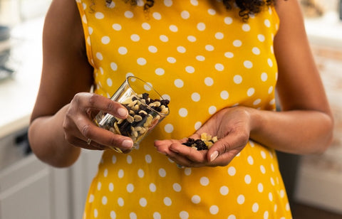 woman in polka dot dress holding a selction of nuts