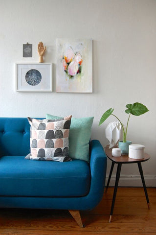 Living room with teal sofa and gallery wall. Artwork by Rae Broyles
