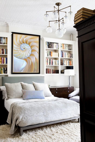 Bedroom with neutral color scheme, artwork by Daniel Sroka