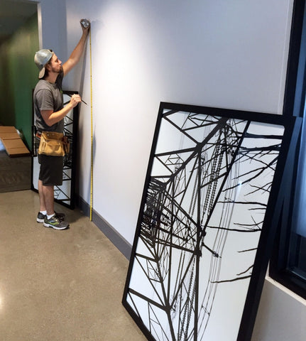 Maxwell Redder, preparator working on an install for one of Art Design Consultants' (ADC) clients