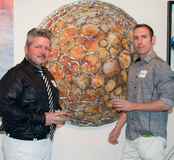 "Collin Rowland and Daniel Augur standing in front of Augur's piece ""Lunar Reflections"" 