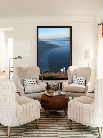 White living room/sitting area with artwork by Grace Berge