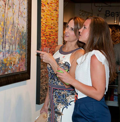 Karen Rolfes and guest looking at artwork | Art Comes Alive 2014 | Art Design Consultants