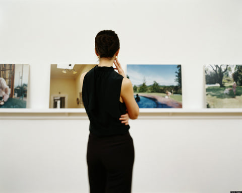 this is an image of a woman looking at art for the blog how to submit your work to galleries and get results.