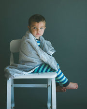 boy with Little Unicorn Chenille Receiving Blanket in Grey