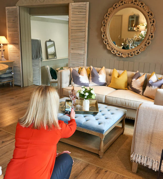 La Residence Interiors' Sarah Cook taking a photo of ottoman in showroom