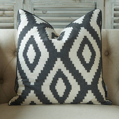 Grey and white cushion with a Mexican inspired diamond pattern