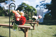 Jars of flowers decorate the ceremony aisle
