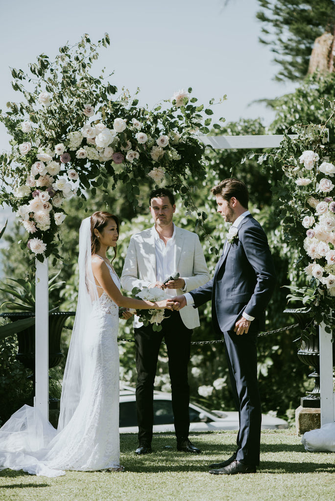 Bride and Groom wedding ceremony under floral arch