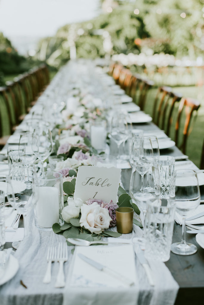 Long reception tables with foliage and floral garland for wedding reception