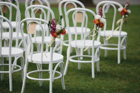 Florals attached to chairs mark the wedding aisle.