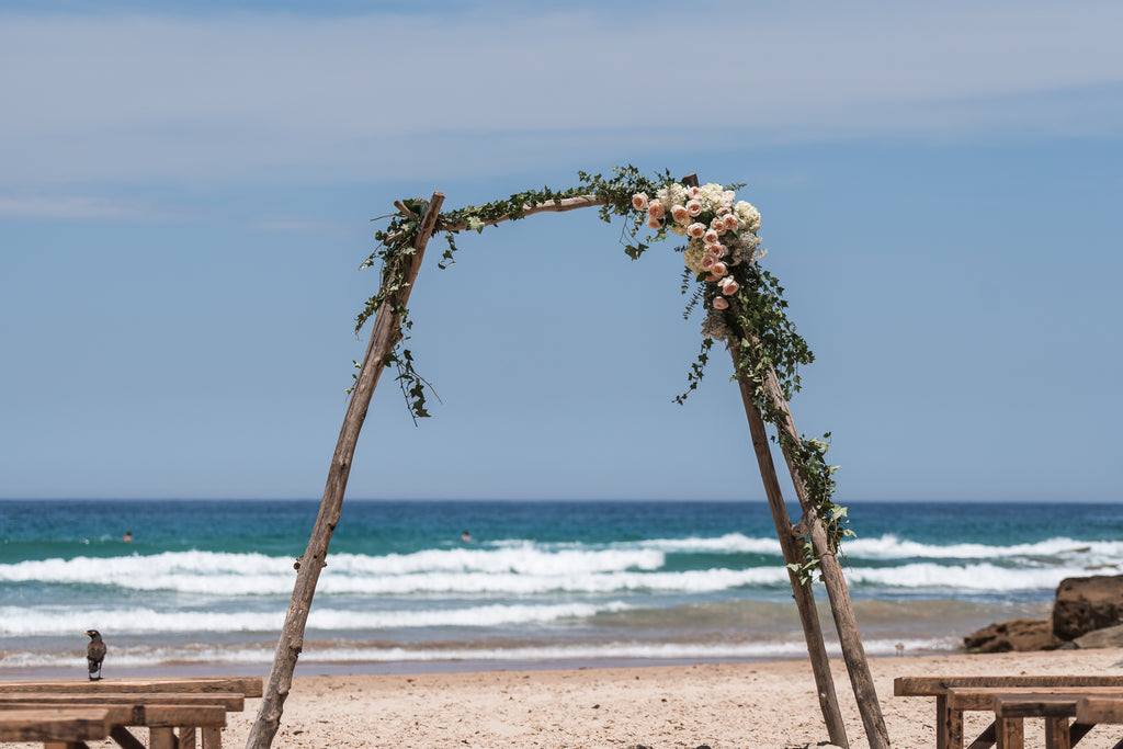 Driftwood arch decorated with florals at Freshwater beach