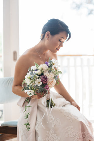 Bride sitting with her garden style bouquet.