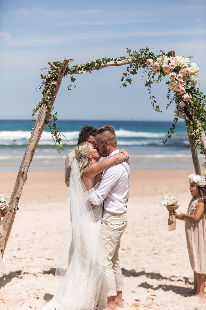 Bride and Groom under driftwood arch at beach wedding