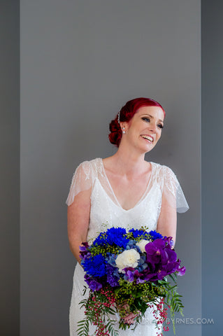 Laughing Bride holding her bouquet in blues and purples.