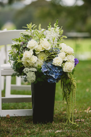 A large arrangement featuring white garden roses.