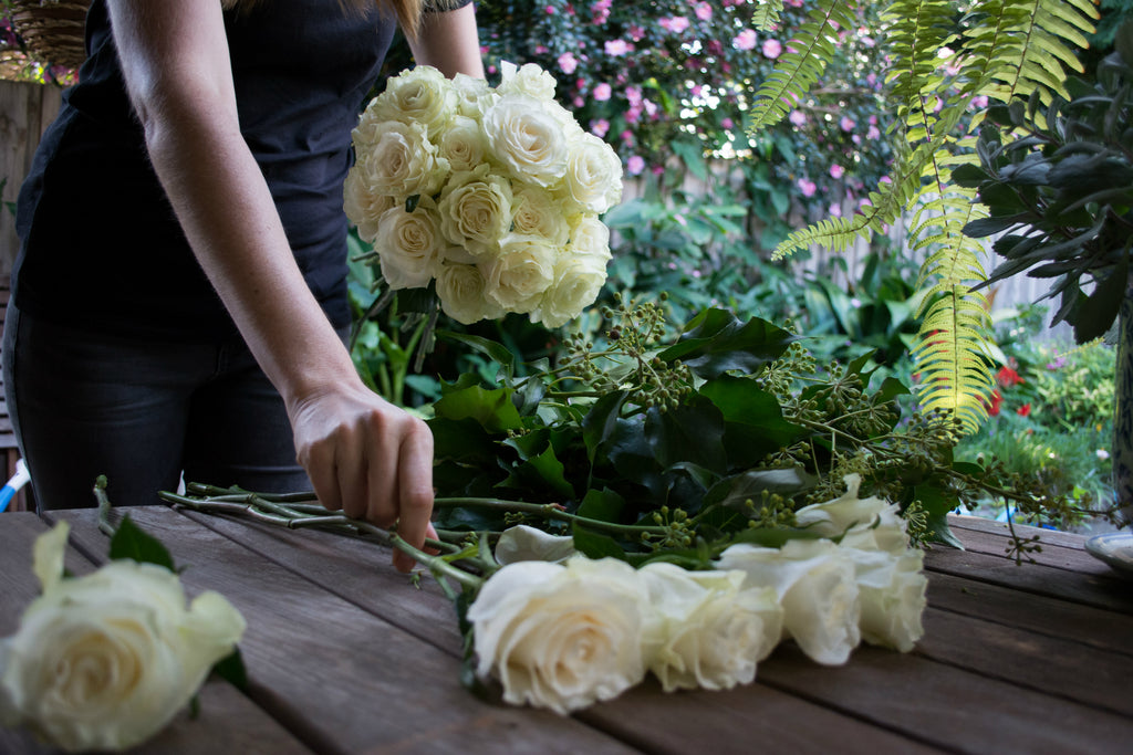 Florist making a white rose bridal bouquet