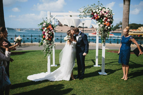 Wedding ceremony in front of floral arbor on Sydney harbour.