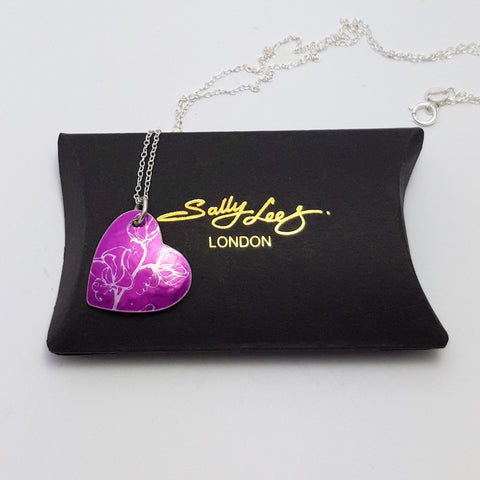 Pink heart pendant with silver coloured linear print of sweet pea flowers on a pink back ground with a silver chain. The pendant is on a pillow shaped black gift box with the Sally Lees logo in the centre in gold.