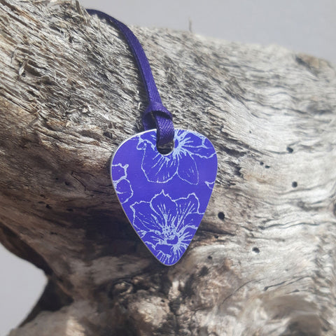 Front view of a purple Guitar pick pendant decorated with a delicate linear print in a silvery colour of larkspur flowers. The pendant has a purple satin ribbon and is hung over a wooden log that has been bleached by the sea.