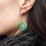 This photograph shows the green side of the reversible women's suffrage earrings. These earrings are circular with the pattern of the end of a scroll in a silvery colour on a green background. They hang on a silver hoop and are photographed on a model.