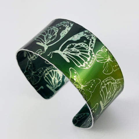 Anodized aluminum cuff printed with butterflies and dyed a dark green and lighter green