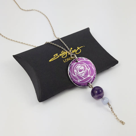 Round, purple, aluminium pendant with printed rose pattern on a sterling silver chain with a purple amethyst bead and a smaller agate bead bead