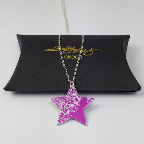 Bright pink star pendant hand crafted from anodised aluminium and printed with a silvery coloured print of an aster flower displayed on a silver chain on a black gift box with the Sally Lees Logo in goil foil