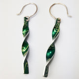 Green aluminium twist earrings with a lily of the valley flower print on both sides with silvery coloured edges and silver hook wires.