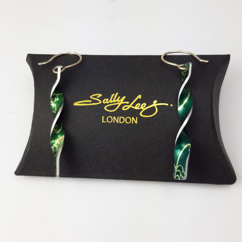 Green aluminium twist earrings with a lily of the valley flower on both sides with silvery coloured edges displayed on a black pillow shaped box with a gold embossed Sally Lees London logo on it.