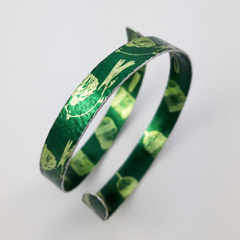 Green, anodised, aluminium cuff printed with small birds on the outside and bird cages on the inside. Called 'The bird has flown'
