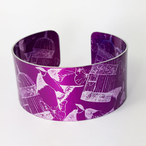 Front view of a cuff with dark magenta background with swallows butterflies and delicate bird cages illustrations in a silvery colour. The butterflies overlap the bird cages and the birds appear to fly up from the bottom of the cuff to the top of the cuff. The patterned inside of the cuff can also be viewed on this photograph.