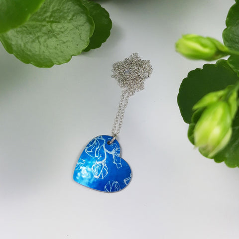 Blue heart pendant with linear print of sweet pea flowers. Pendant has a silver chain.