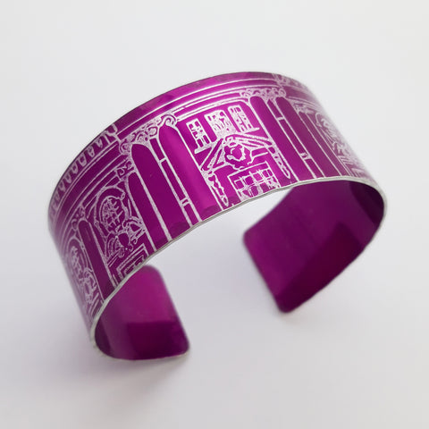Bright magenta cuff with an architectural drawing of part of a grand building including windows and the top of a door way