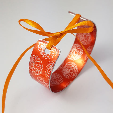 Bright orange cuff with marigold flower illustrations in a silvery colour reapeted on the inside and outside of the cuff. The ends of the cuff are visible with a hole in each end centrally placed and an orange ribbon through the holes and tied in a bow