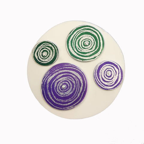 Round white aluminium brooch decorated with two purple and two green disks of different sizes with silvery coloured scroll motifs on them. The disks are riveted onto the white disk with siver rivets.