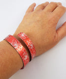 Anodized aluminum wrap around cuff in citrus orange with silvery coloured printed floral pattern on wrist of adult women