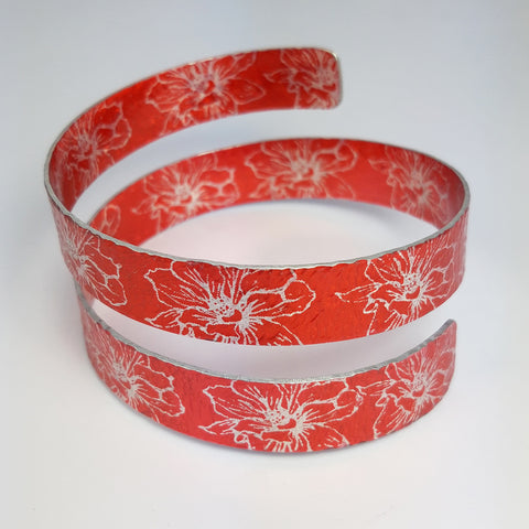 Anodized aluminum wrap around cuff in citrus orange with silvery coloured printed floral pattern