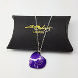 Purple heart shaped pendant with a line drawing of a cute finch seen from the side printed in a silvery colour covering the surface of the heart. The bird has a berry in its beak. The pendant is displayed on a black pillow shaped box with the Sally Lees logo embossed in gold.  The silver chain is draped over the box.