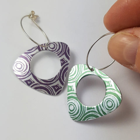 Triangular earrings with rounded edges with circular holes centrally placed in each earring. The earrings are made from anodised aluminium and are different colours - one green and one purple. The patterns on each earring are many concentric circles next to each other in a uniform pattern. The earring wires are eliptical shaped and the earring on the right is held between a finger and thumb of a human hand.
