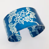 Hand made anodised aluminium cuff decorated with large prints of carnations. and dyed teal.
