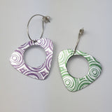 Pair of triangular drop anodised aluminium patterned with concentric circles. One earring is green with a silvery coloured pattern and one is purple with a silvery pattern. Each earring has a lage circular hole in the middle.